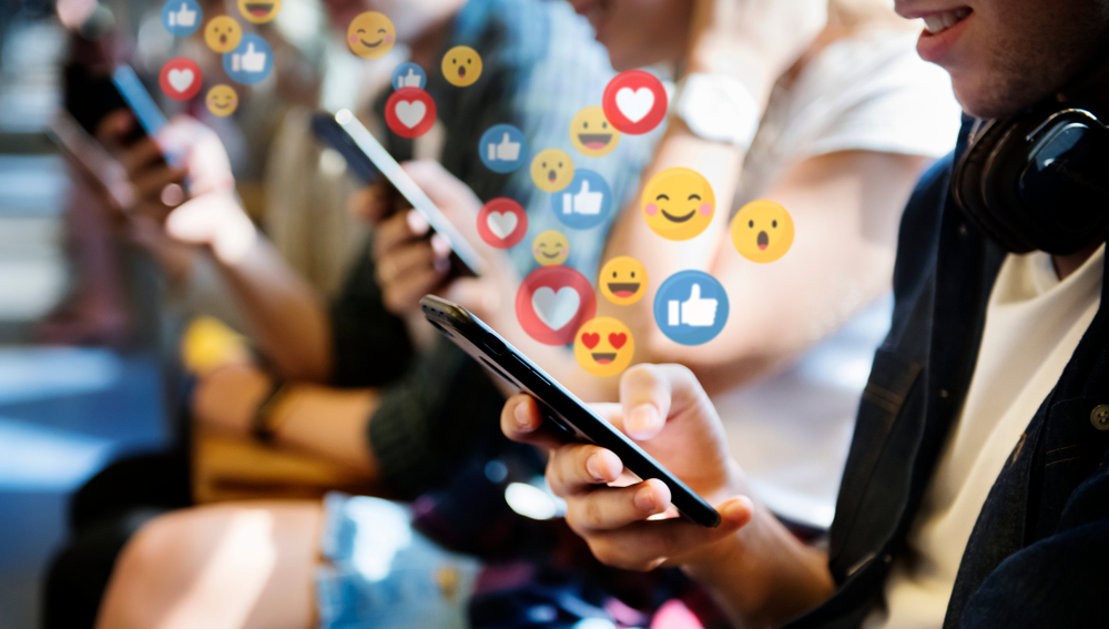 A group of people on their phones with Facebook react icons hovering above their mobiles