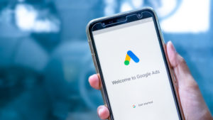 """Hand holding phone with """"welcome to Google Ads"""" on screen"""
