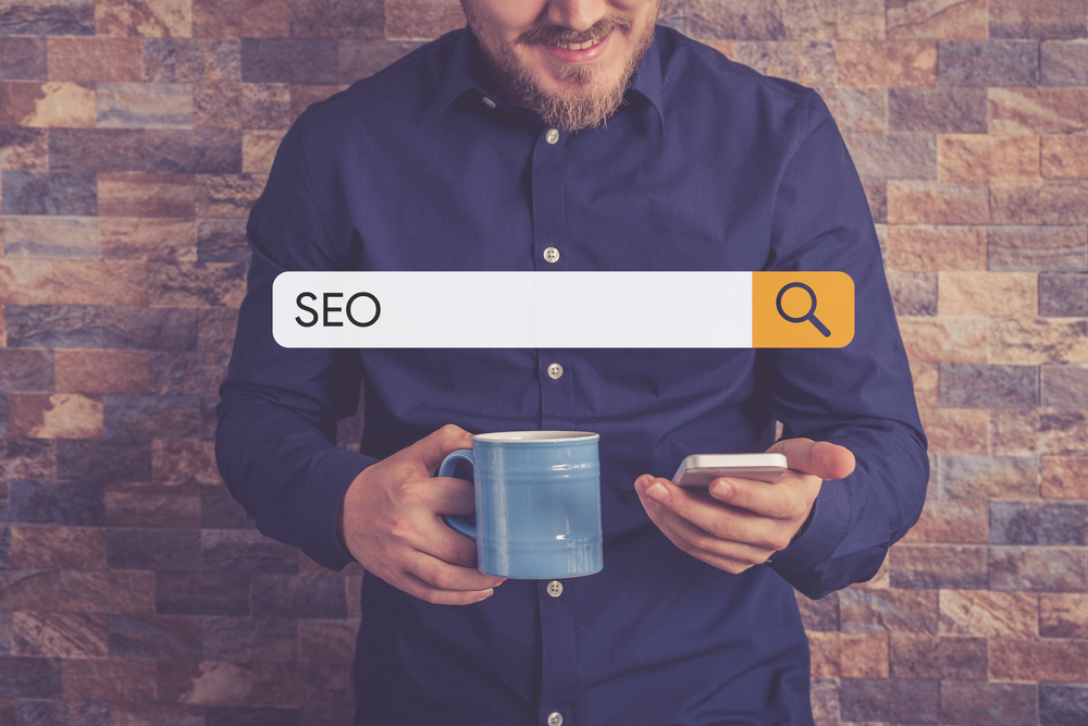 "Person in blue shirt holding a phone and a mug. Search bar with ""SEO"" over the top."